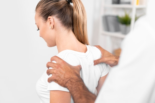 Male physiotherapist checking woman's back shoulders