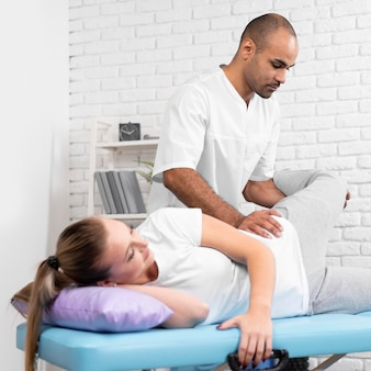 Male physiotherapist checking woman's hip