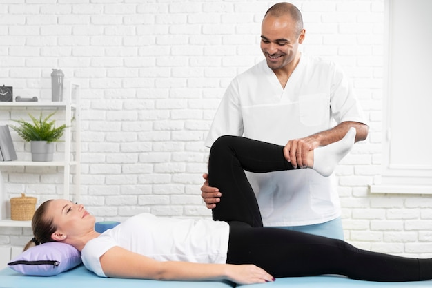 Male physiotherapist checking woman's leg flexibility