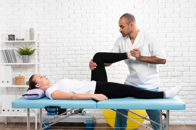 Male physiotherapist checking woman's leg