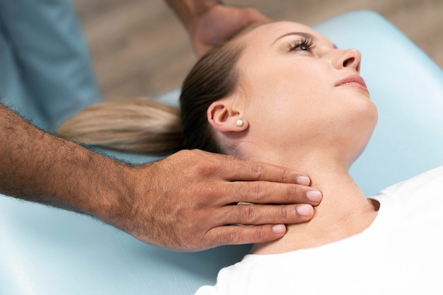 Male physiotherapist checking woman's neck while sitting on bed