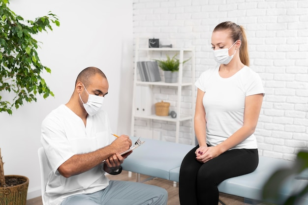 Male physiotherapist checking woman