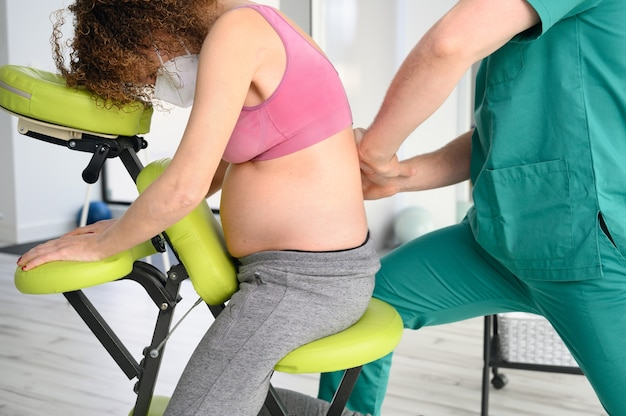 Male physiotherapist cures back pain of a pregnant woman.