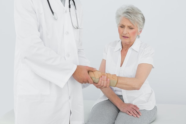 Male physiotherapist examining a senior womans wrist