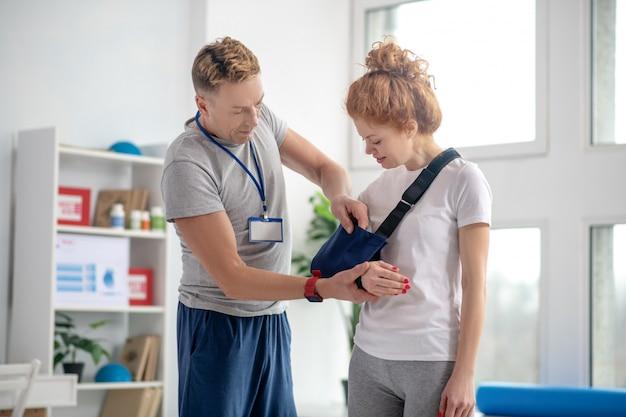 男性の理学療法士、女性患者の腕スリングを修正