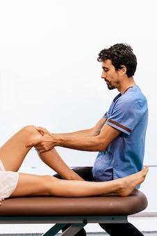 들것에 누워있는 여자에게 마사지를주는 남성 물리 치료사