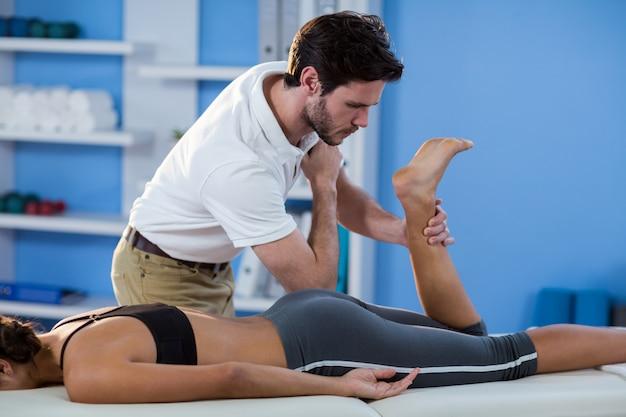 男性の理学療法士が女性患者に股関節マッサージを与える