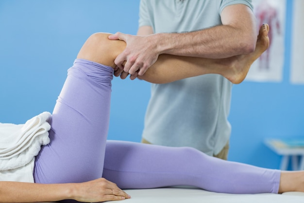Male physiotherapist giving knee massage to female patient