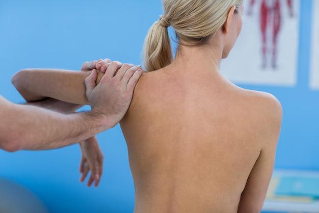 男性の理学療法士が女性患者に肩のマッサージを与える
