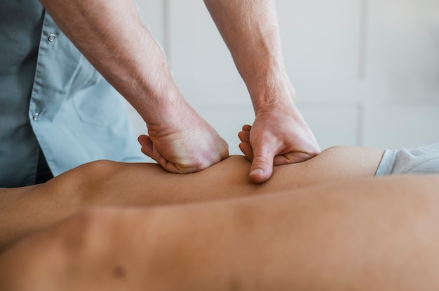 Male physiotherapist on a massage session with female patient