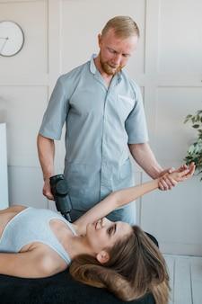 Fisioterapista maschio con paziente femminile e attrezzature durante una sessione di terapia fisica