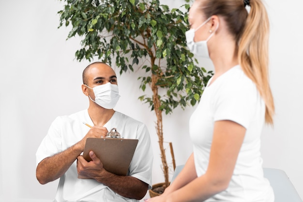 의료 마스크 및 클립 보드 확인 여자와 남성 물리 치료사