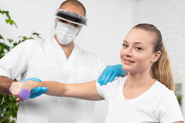 Male physiotherapist with medical mask and face shield checking woman's arm