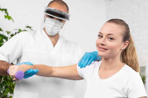 Fisioterapista maschio con maschera medica e schermo facciale che controlla il braccio della donna