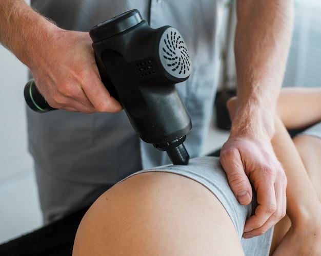 Fisioterapista maschio con donna e attrezzatura durante una sessione di terapia fisica