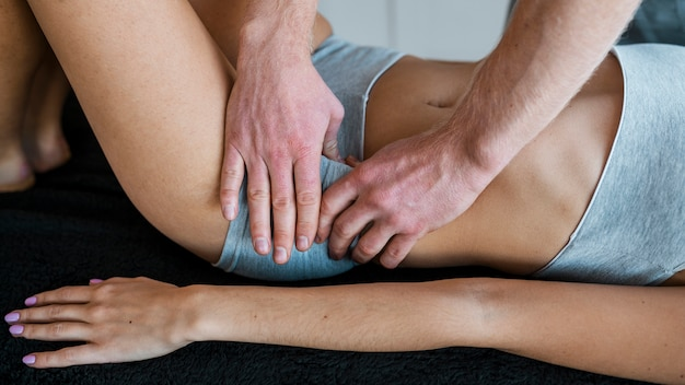 Fisioterapista maschio e donna durante una sessione di massaggio