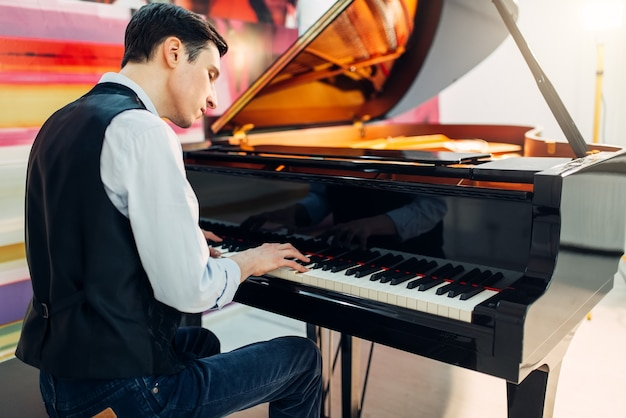 Male pianist at the classical black grand piano