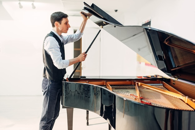 Male pianist opens the lid of black grand piano