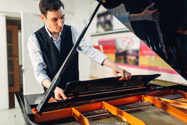 Пианист открывает крышку черного рояля