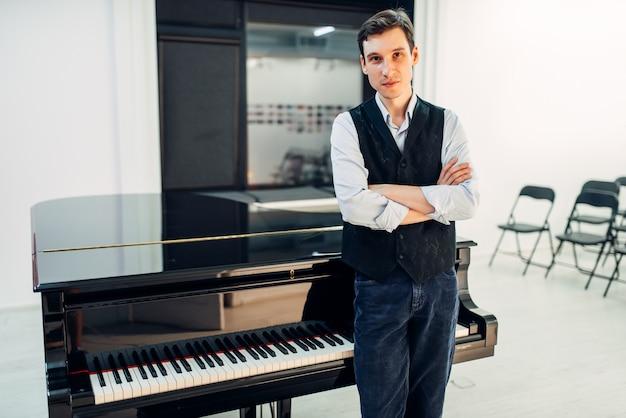 Пианист стоит у черного рояля