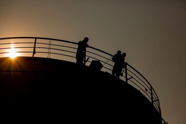 남성 사진 실루엣 빔 햇빛이 검사 두께 산업의 난간을 건너고 있습니다.
