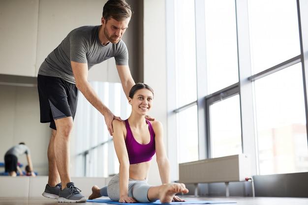 柔軟な女の子の背中を調整する男性のピラティスコーチ