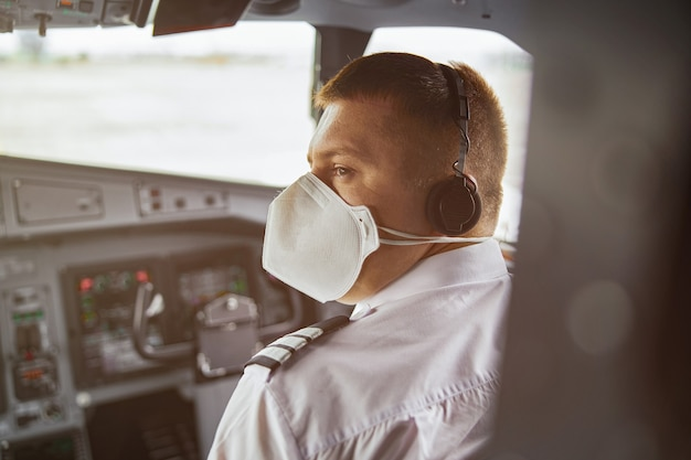 Male pilot in cockpit of passenger airplane jet. back view of european man wear uniform, medical mask and headphones. civil commercial aviation. air journey concept