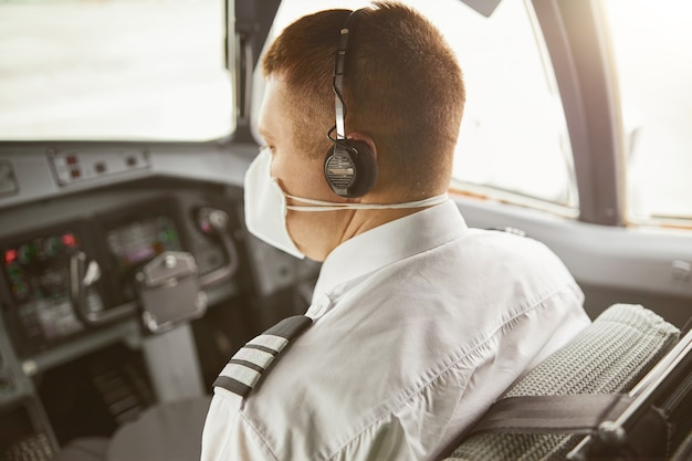 Male pilot in cockpit of passenger airplane jet. back view of european man wear uniform, medical mask and headphones. civil commercial aviation. air travel concept