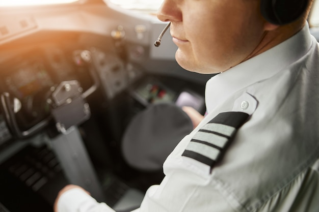 Male pilot in cockpit of passenger airplane jet. close up of man wear uniform and headphones. obscure face. civil commercial aviation. air travel concept