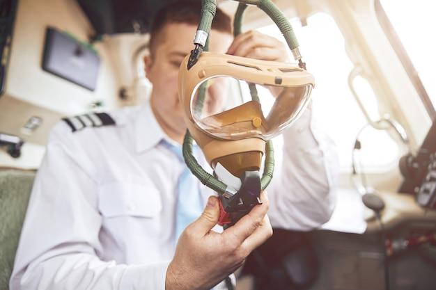 Male pilot holding air mask in cockpit of airplane jet. modern passenger plane. european man wear uniform. civil commercial aviation. air travel concept