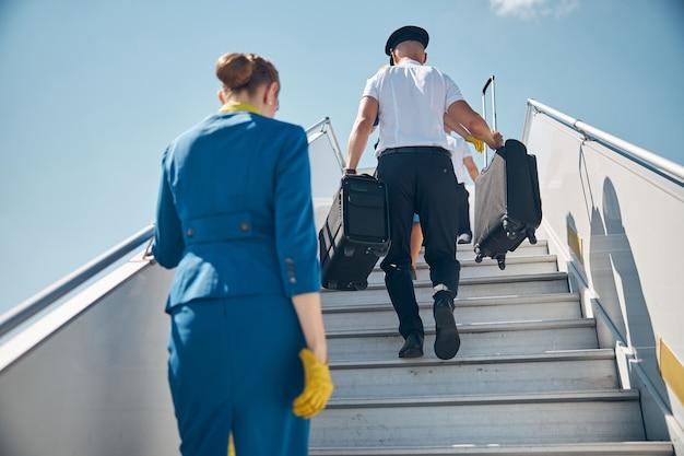 Пилот-мужчина держит дорожные чемоданы и поднимается по ступенькам самолета, пока стюардесса идет позади человека