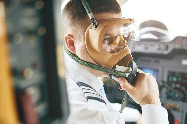 Male pilot take off air mask in cockpit of airplane jet. modern passenger plane. european man wear uniform. civil commercial aviation. air travel concept