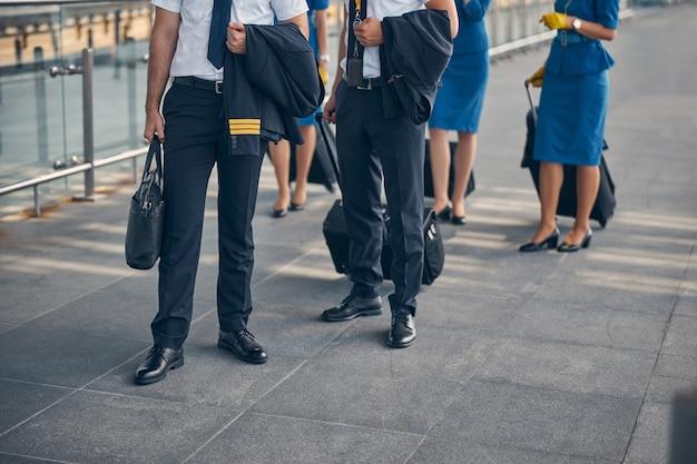 Пилоты-мужчины с куртками на руках держат дорожные сумки, а стюардессы в синей форме стоят позади мужчин