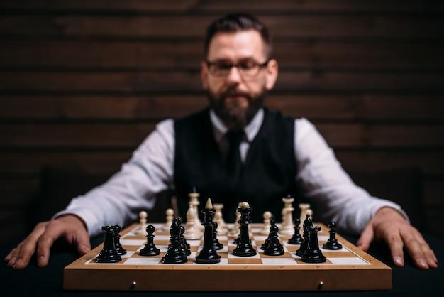 Игрок мужского пола против шахматной доски с набором фигур