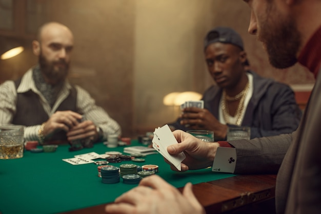 Male player cheating in poker at gaming table, casino. addiction, risk, gambling house