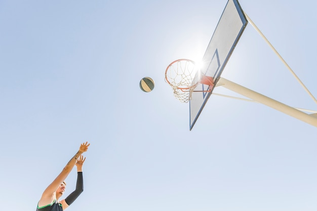 A male player throwing basketball in the hoop against clear blue sky