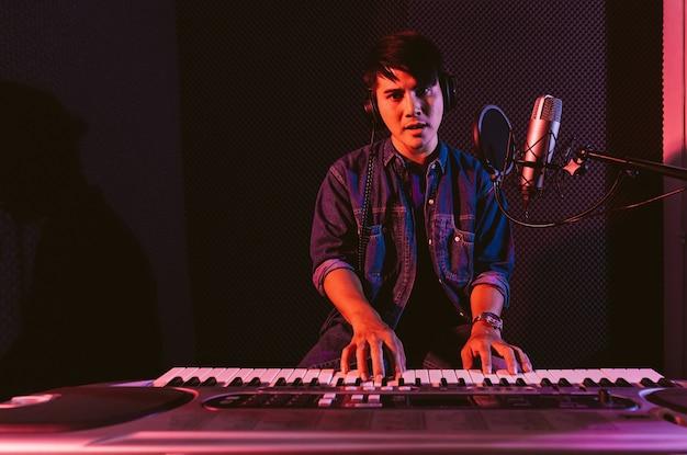 Мужчина играет на электрической клавиатуре в наушниках запись песен