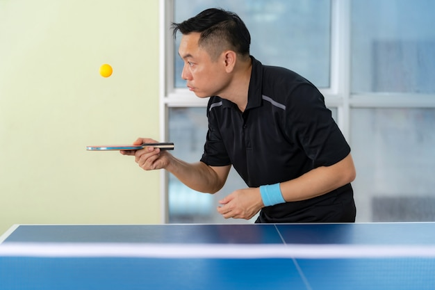 Male playing table tennis with racket and ball in a sport hall