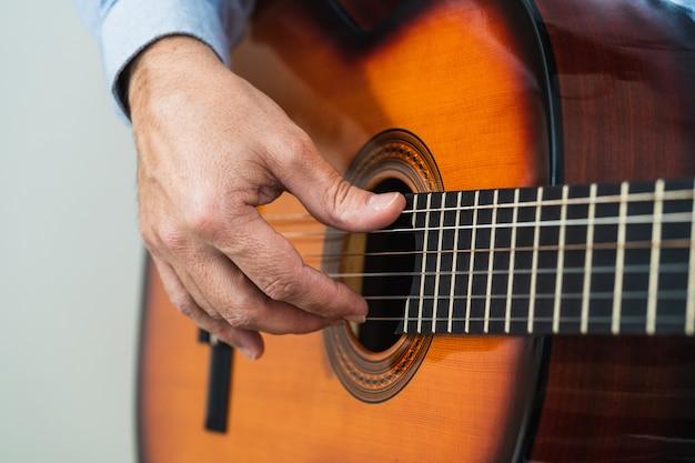 ギターの弦を弾く男性。オンラインコースでの練習と学習