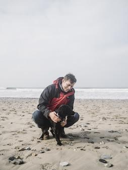 낮 동안 해변에서 귀여운 검은 발 바리 강아지와 함께 노는 남성