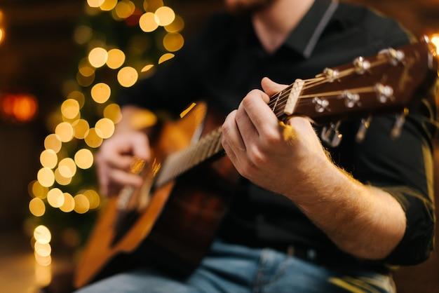 男性はギターのクローズアップを演奏します。ボケ味のある装飾が施されたクリスマスツリーを背景に。