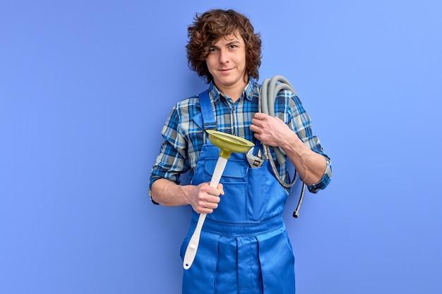 プランジャーを保持し、青い壁のカメラに微笑んで男性配管工