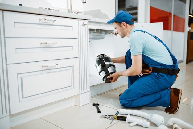 Сантехник-мужчина в униформе устанавливает на кухне измельчитель. разнорабочая с сумкой для инструментов ремонт раковины, сервис сантехники на дому