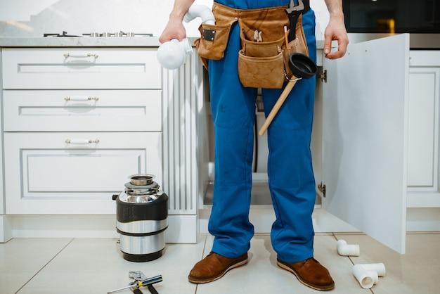 Водопроводчик-мужчина устанавливает фильтр для воды на кухне. разнорабочая с сумкой для инструментов ремонт раковины, сервис сантехники на дому
