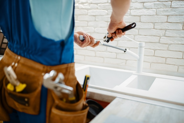 Male plumber in uniform fixing faucet in the kitchen. handyman with toolbag repair sink, sanitary equipment service at home