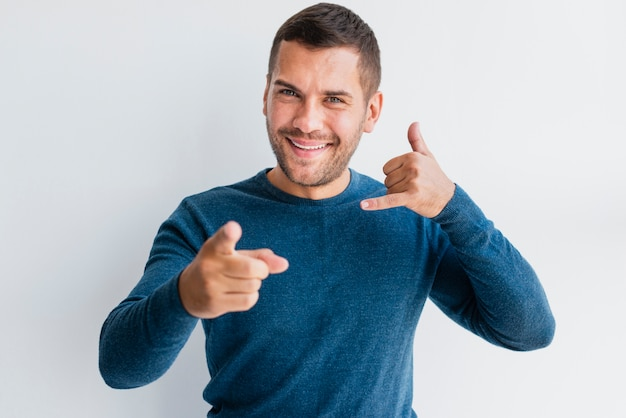 Male pointing at camera with calling hand sign