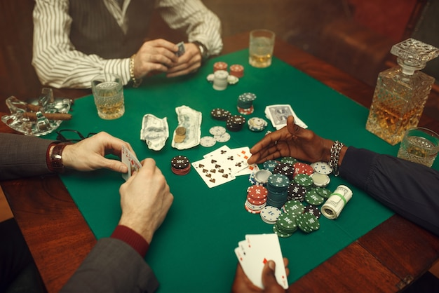 Male poker players at gaming table with green cloth