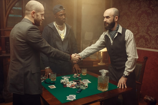 Male poker players shake hands in casino. addiction, risk, gambling house