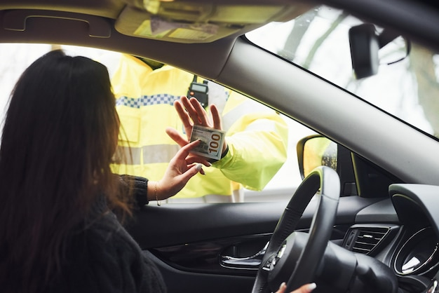 Male police officer in green uniform refuse to take bribe from woman in vehicle.