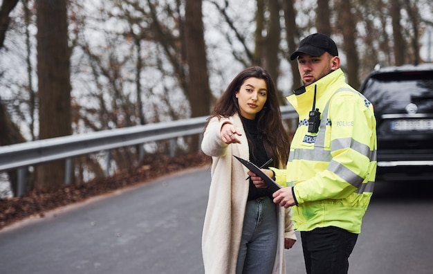 Male police officer in green uniform talking with female owner of the car on the road.
